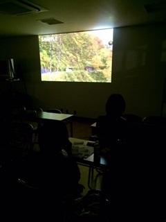 上映中の様子(スクリーンには紅葉しはじめた木々)